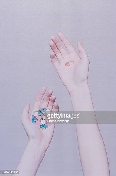 One hand holding many pills the other holding one