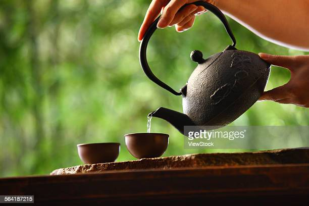 One hand holding the teapot in tea