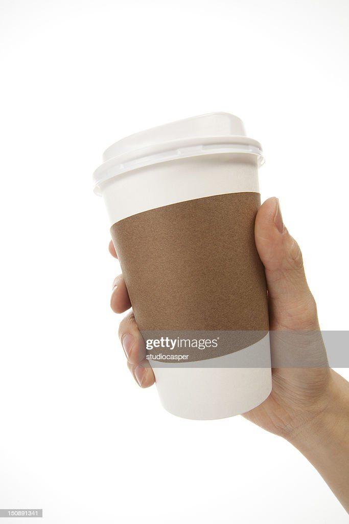 One hand holding white coffee cup with brown cup holder : Stock Photo