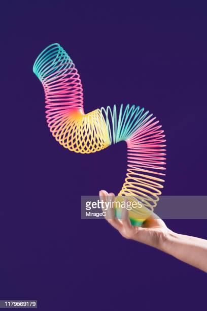 one hand playing with colorful coil toy - espiral de metal - fotografias e filmes do acervo
