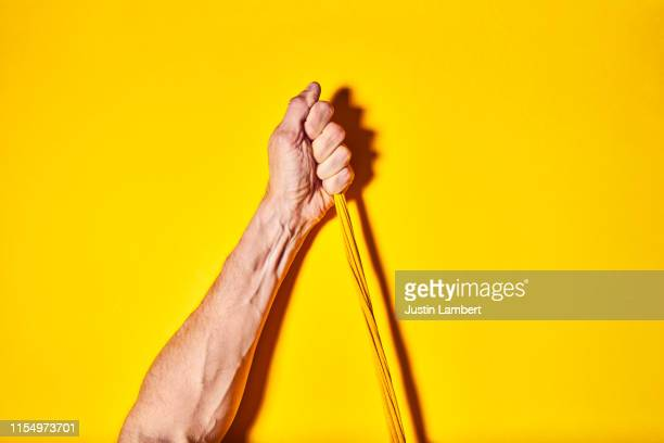 One hand pulling twisted yellow cord upwards on a bright yellow backdrop