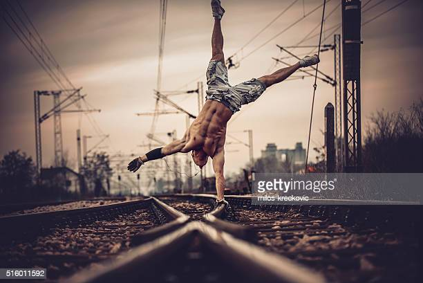 One hand stand on railroad tracks