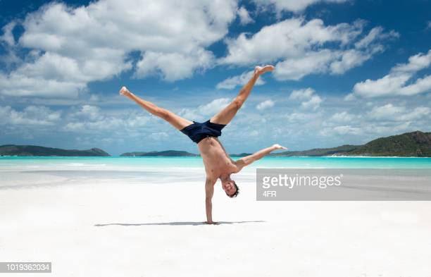 one handed stand, capoeira acrobatic yoga pose, whitsunday islands, queensland, australia - handstand stock pictures, royalty-free photos & images
