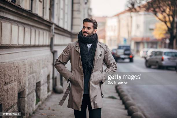 one handosme man dressed in warm winter clothing walking outdoors in the city - coat imagens e fotografias de stock