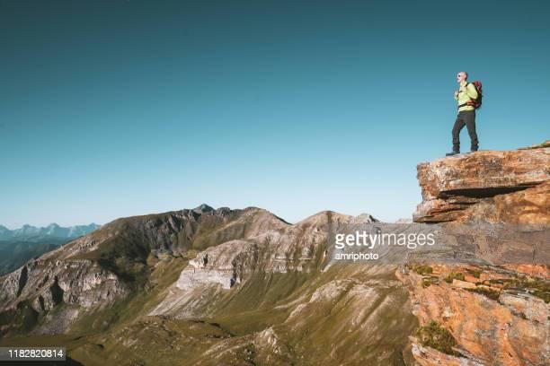 ein wanderer steht allein auf dem berggipfel mit blick auf die alpen - aktiver lebensstil stock-fotos und bilder