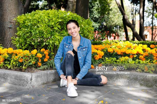 one hispanic teenage girl sitting on the floor in front of flowers in bloom in mexico city, mexico - beautiful mexican girls stock photos and pictures