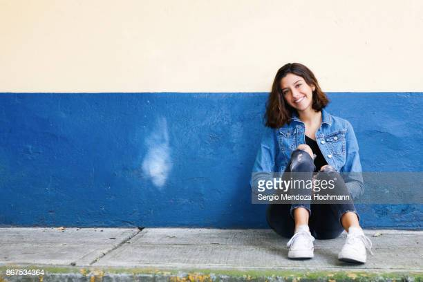 one hispanic teenage girl sitting on the floor in mexico city, mexico - blue jacket stock pictures, royalty-free photos & images