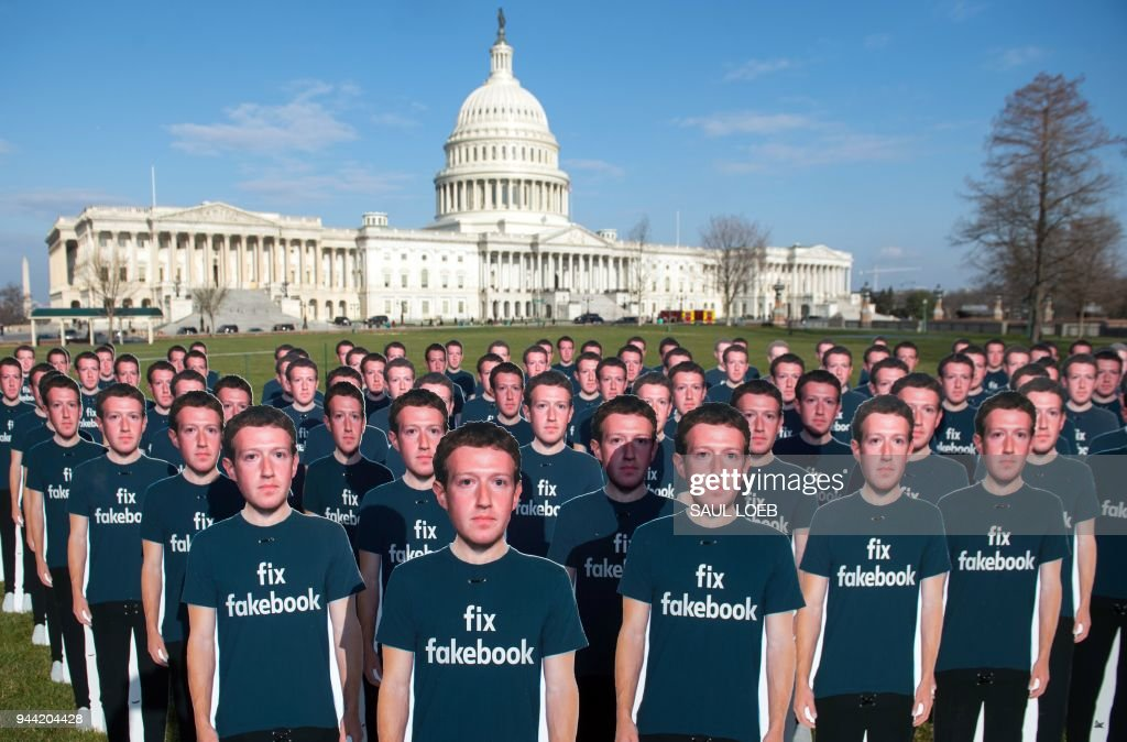 TOPSHOT - One hundred cardboard cutouts of Facebook founder and CEO Mark Zuckerberg stand outside the US Capitol in Washington, DC, April 10, 2018. - Advocacy group Avaaz is calling attention to what the groups says are hundreds of millions of fake accounts still spreading disinformation on Facebook.
