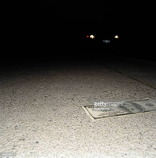 One hundred dollar bill on street at night, car approaching behind