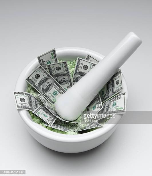 US one hundred dollar bills in mortar with pestle, elevated view
