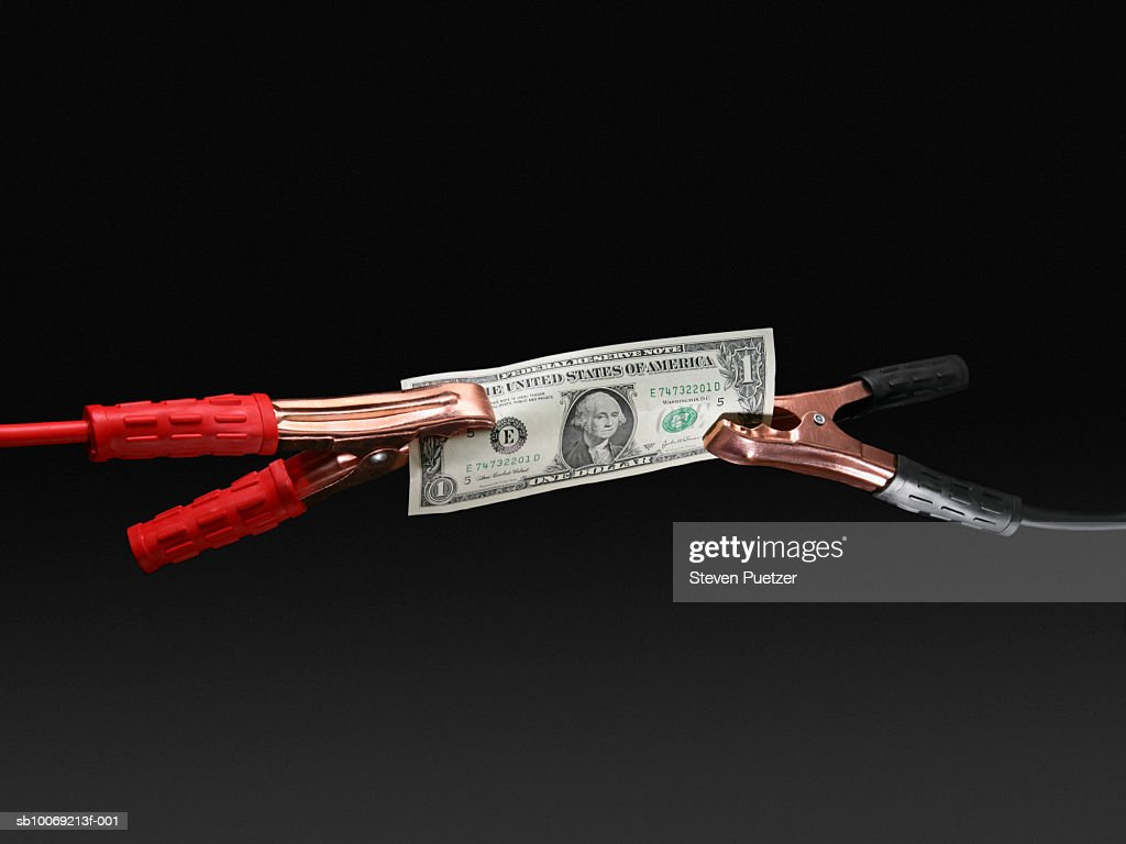US one hundred dollar connected to jumper cables, close-up : Stockfoto
