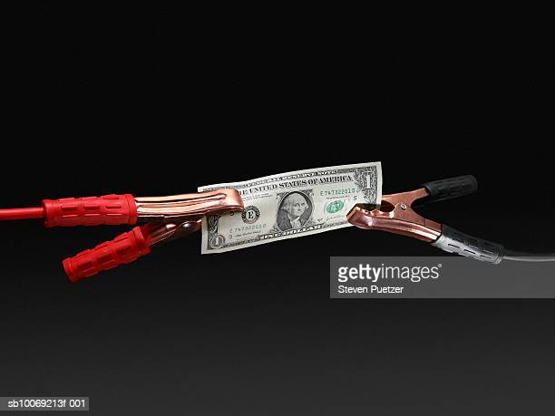 US one hundred dollar connected to jumper cables, close-up