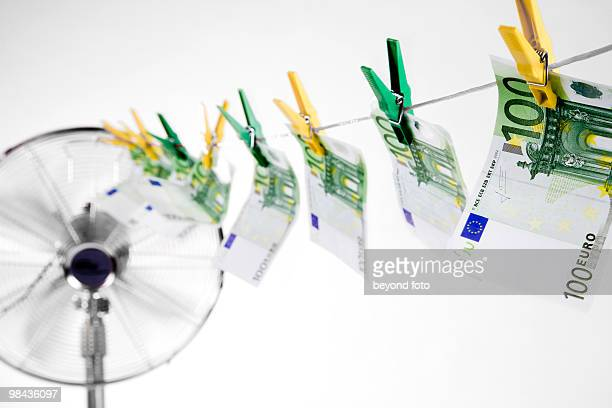 one hundred euro banknotes hanging on clothesline dryed by fan - money laundering stock photos and pictures