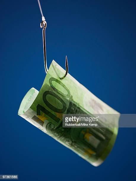 One hundred Euros banknote on hook, against blue background