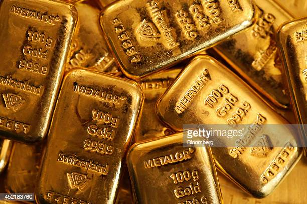 One hundred gram gold bars are seen in this arranged photograph at Gold Investments Ltd bullion dealers in London UK on Tuesday July 15 2014 Gold...
