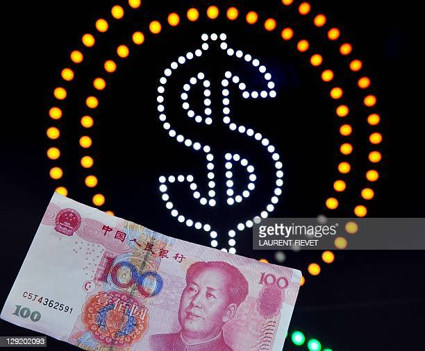 A one hundred yuan bank note is seen in front of a US dollar sign in Hong Kong on October 14 2011 China reacted furiously to a US Senate vote to pass...