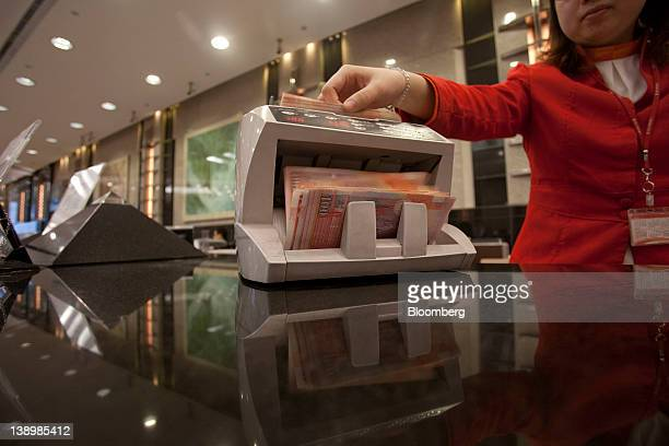 One hundreddollar Hong Kong banknotes pass through a currency counting machine in an arranged photograph in the Bank of East Asia Ltd main branch in...