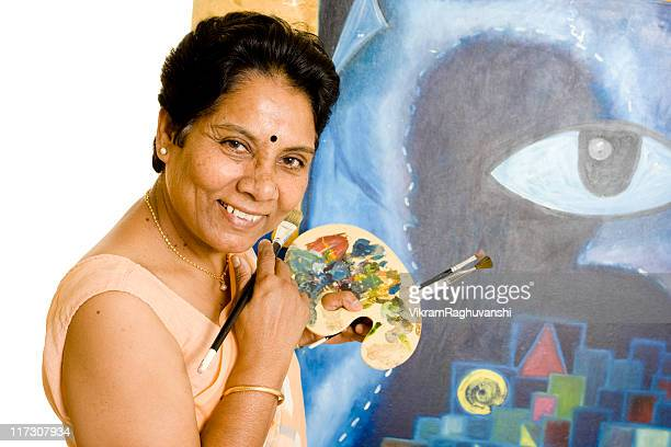 One Indian Senior Woman Artist Working on her Painting