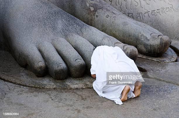 One Jain pilgrim is praying at the feet of the gigantic staue of Gomateshwara in Sravanabelagola