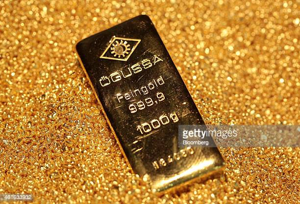 A one kilogram gold bar sits on a pile of fine gold grains following production at Oegussa GmbH's gold and silver separating plant a unit of Umicore...