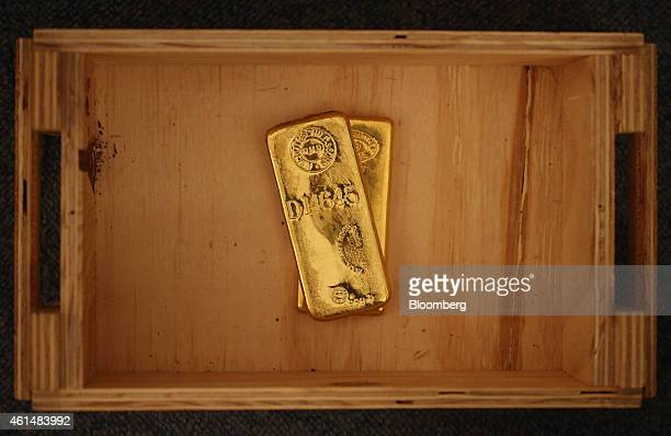 One kilogram gold bars sit in a wooden storage box in this arranged photograph taken at Gold Investments Ltd bullion dealers in London UK on Tuesday...