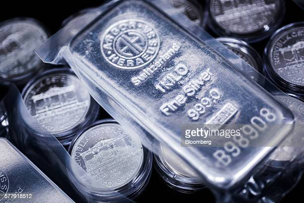 A one kilogram silver bar produced by Swiss manufacturer Argor Hebaeus SA sits on top of Austria Vienna Philharmonic commemorative silver coins...