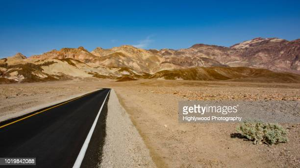 one lane through: artist's drive death valley - highlywood stock photos and pictures
