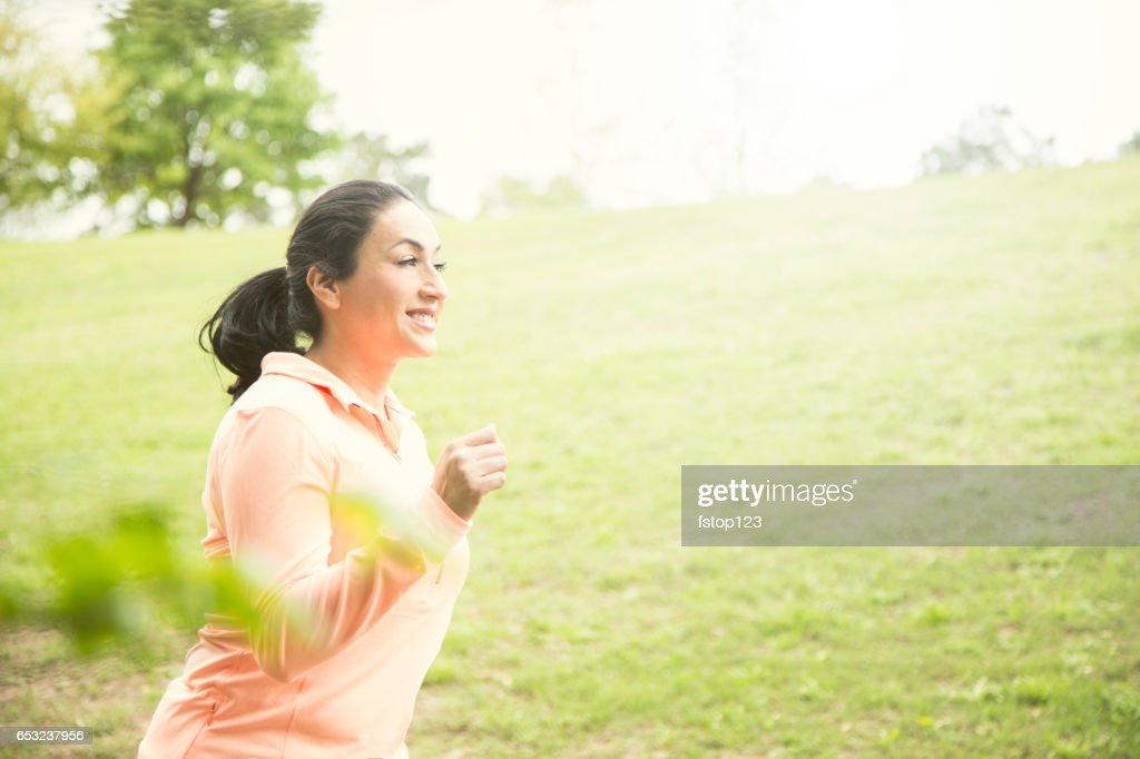 One Latin descent woman running in neighborhood park. : Foto stock