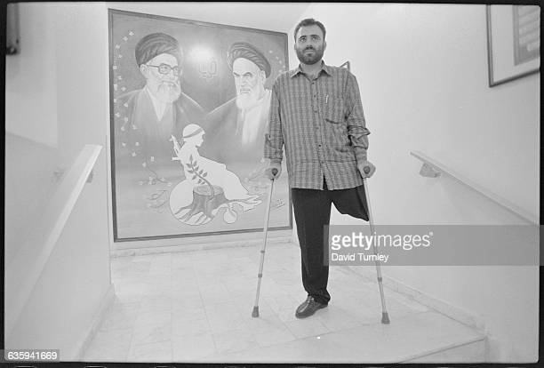 A one legged man stands on crutches in front of a painting featuring the Ayatollahs Ali Khamenei and Ruhollah Khomeini and the silhouette of a person...