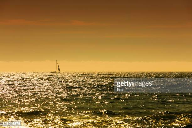 One lonely sailboat in the open sea at a colorful sunset