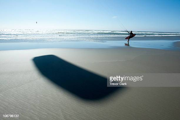 One male kitesurfer walking out into the ocean with the shadow of his kite prominent in the foreground.