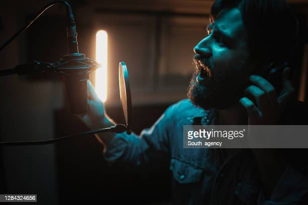 one male singer recording song in music studio - country and western stock pictures, royalty-free photos & images