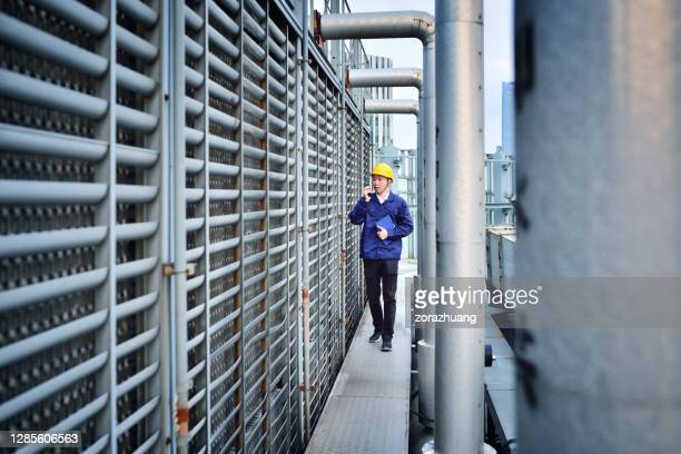 one males engineer examining at pipeline - cooling tower stock pictures, royalty-free photos & images