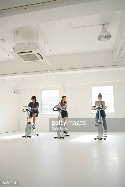 One man and two women on stationary bikes