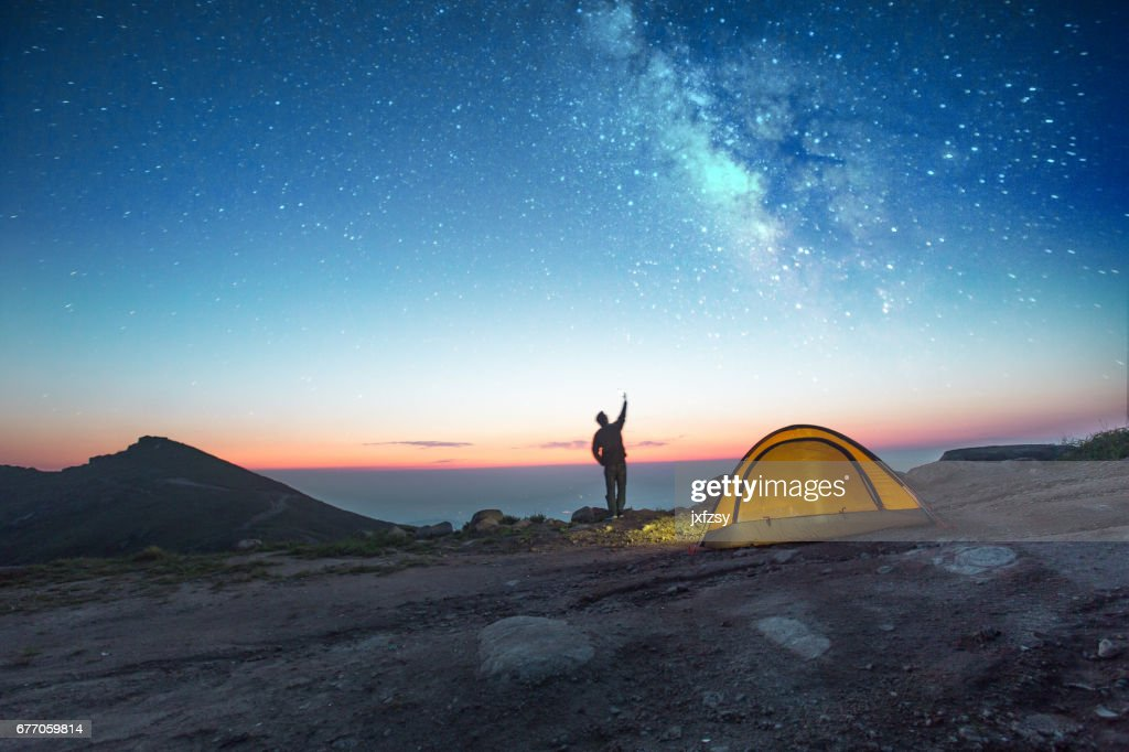 one man camping at night with phone : Stock Photo