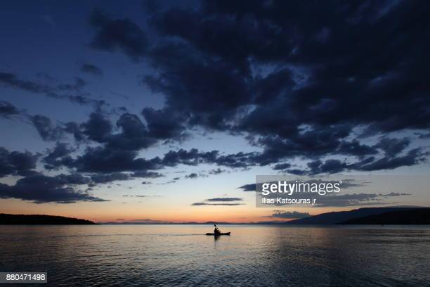 One man canoeing in calm sea under dramatic sky at sunset