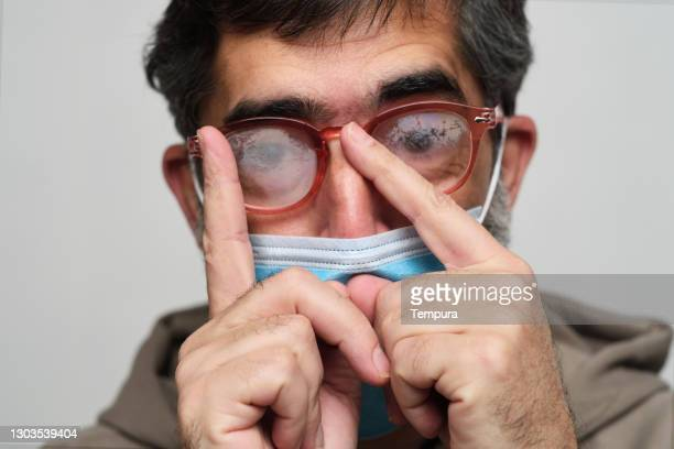 one man cleaning his glasses stained with breath vapor. - one man only stock pictures, royalty-free photos & images