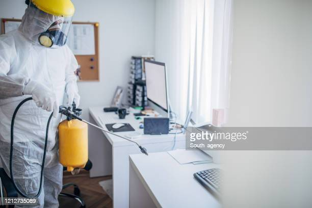 one man in protective suit disinfecting office work space - protective suit stock pictures, royalty-free photos & images