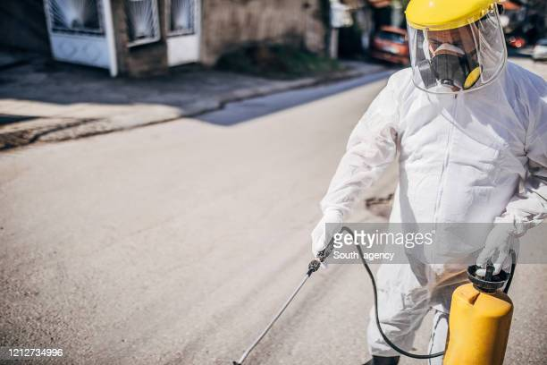 one man in protective suit disinfecting outdoors and spraying the contaminated street - cleaning agent stock pictures, royalty-free photos & images