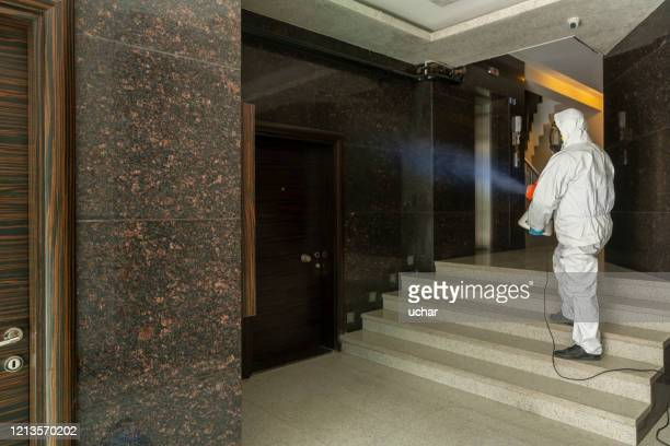 one man in protective suit disinfecting the apartment entry - disinfection stock pictures, royalty-free photos & images