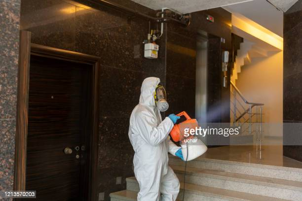 one man in protective suit disinfecting the apartment entry - clorox stock pictures, royalty-free photos & images