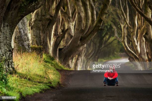 One man is sitting at the dark hedges, Northern Ireland