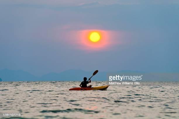 One Man Kayaking at Sunset on Tropical Ao Phra Nang Beach, Railway, Rai Leh, South Thailand, Southeast Asia.