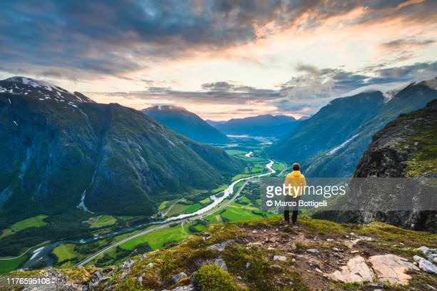 one man looking at view on top of romsdal valley, norway - 谷 ストックフォトと画像