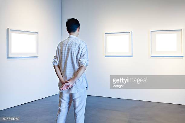 One man looking at white frames in an art gallery