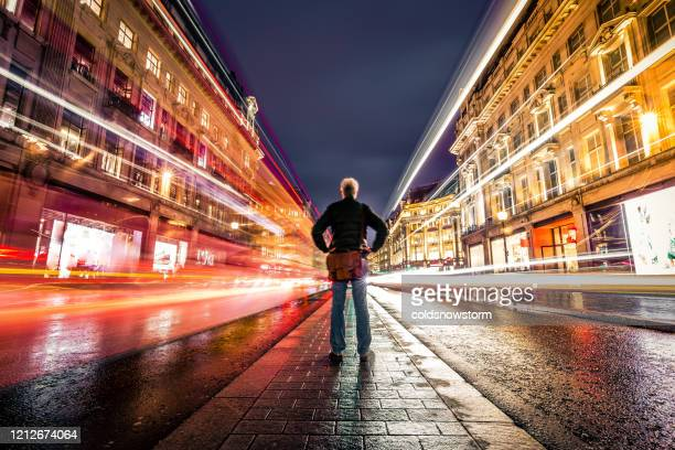 one man on busy city street at night long exposure with blurred motion - back stock pictures, royalty-free photos & images