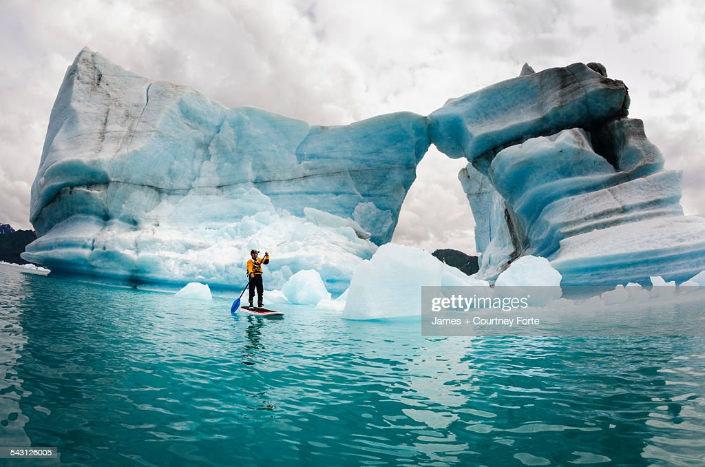 One man on stand up paddle board (SUP) paddles past hole melted in iceberg on Bear Lake in Kenai Fjords National Park, Alaska. : Stock Photo