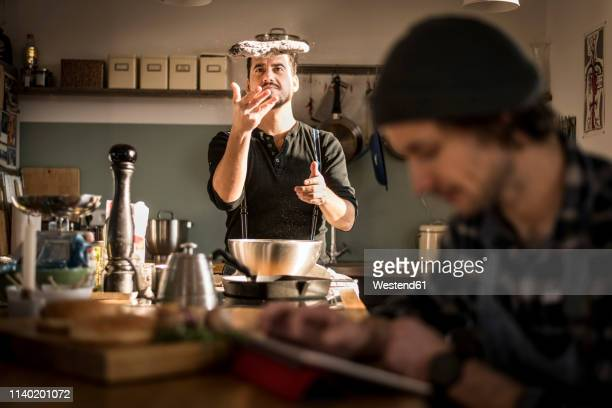 one man preparing bread dough while the other is using his digital tablet - passione foto e immagini stock