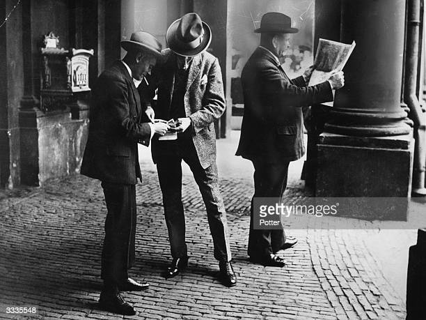 One man provides cover with his newspaper while the other sells dollars on the black market in Berlin