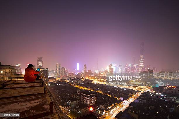 One man reading the smart phone screen on the rooftop,background is Shanghai finance building